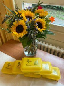 Blumenstrauß und Stapel gelber Brotdosen